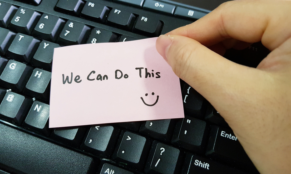 """sticky note on keyboard saying """"we can do this"""""""